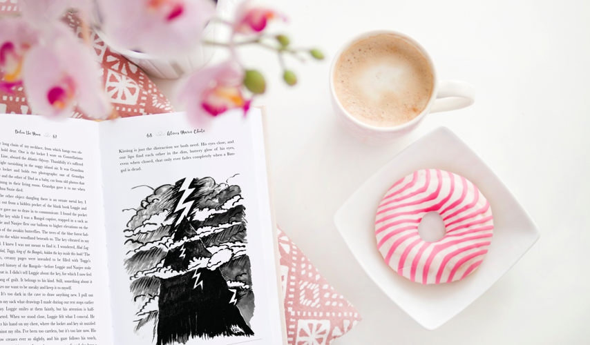 artistic photo of Below the Moon, laid open, with coffee and a pink and white striped donut